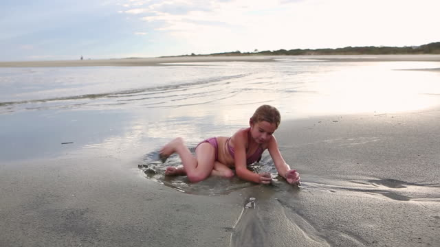 MS Shot of young girl digging in sand at beach / St. Simons Island, Georgia, United States