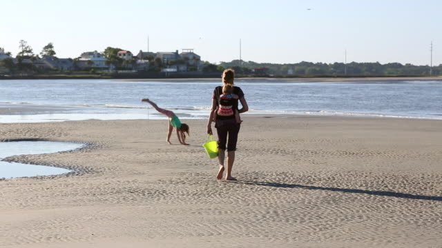 WS TU Shot of young girl doing cartwheels on beach and mother walking with baby on her back / St Simon's Island, Georgia, United States