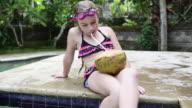 MS TU Shot of young girl drinking fresh coconut milk on side of pool / Ubud, Bali, Indonesia