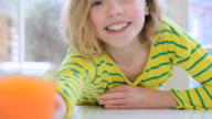 CU Shot of young girl drinking glass of juice and smiling / London, Greater London, United Kingdom