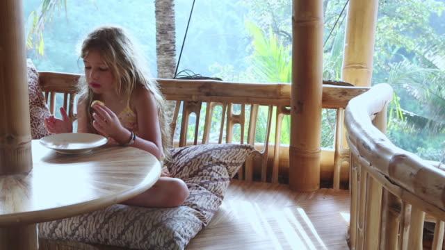 MS PAN Shot of young girl eating on bamboo porch / Ubud, Bali, Indonesia