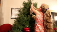 MS Shot of young girl hanging christmas ornaments on tree / Lamy, New Mexico, United States