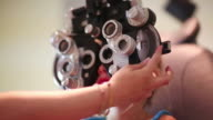 CU R/F Shot of young girl having eye exam / Lamy, New Mexico, United States