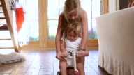 MS Shot of young girl helping her baby brother on his ride toy / Santa Fe, New Mexico, United States