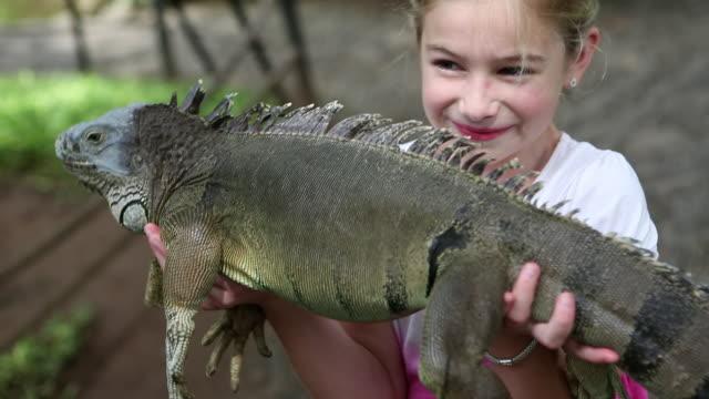 CU R/F Shot of young girl holding large iguana / Ubud, Bali, Indonesia