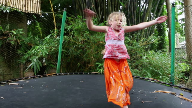 MS Shot of young girl jumping on trampoline / Ubud, Bali, Indonesia
