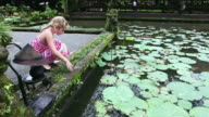 MS Shot of young girl looking at pond full of water lilies / Ubud, Bali, Indonesia
