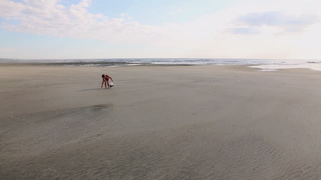 WS Shot of young girl looking for shells at beach / St. Simons Island, Georgia, United States