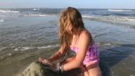 MS TU Shot of young girl making sand castle / St Simon's Island, Georgia, United States