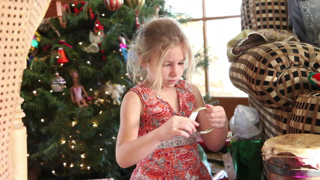 MS Shot of young girl opening gifts on Chrismas morning / Lamy, New Mexico, United States