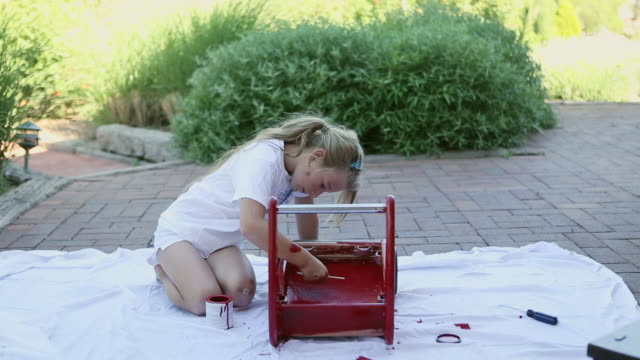 MS Shot of young girl painting red wagon / St Simon's Island, Georgia, United States