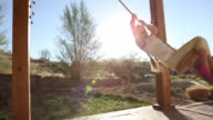 MS Shot of young girl playing on swing on her porch / Lamy, New Mexico, United States