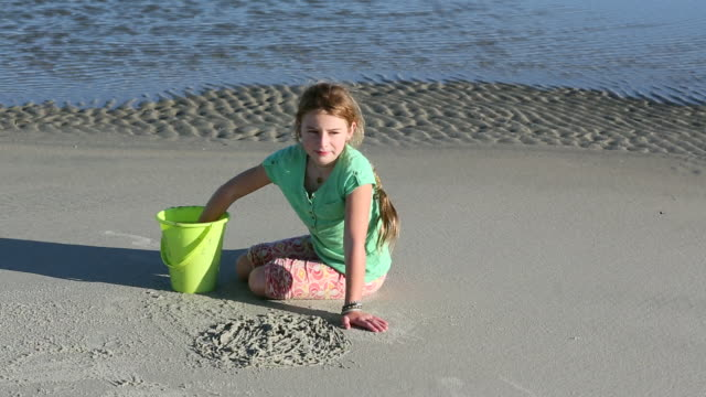 MS Shot of young girl playing with sand on beach / St Simon's Island, Georgia, United States