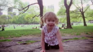 MS Shot of young girl sitting on rock, clapping and smiling / New York, United States