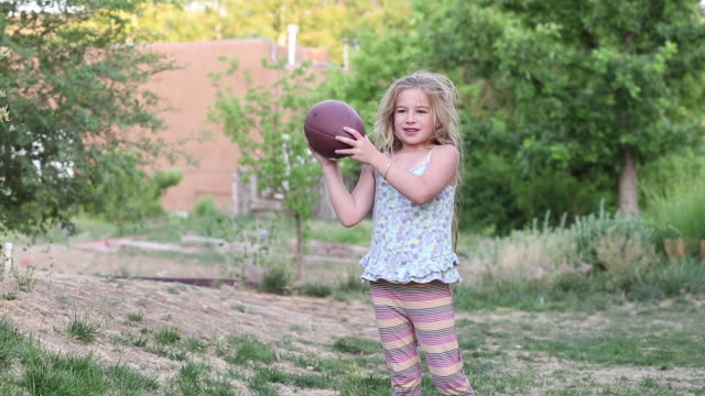 MS Shot of young girl throwing football / Lamy, New Mexico, United States