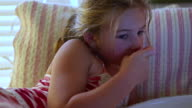 CU TU Shot of young girl watching television and eating popcorn in bed / St. Simons Island, Georgia, United States