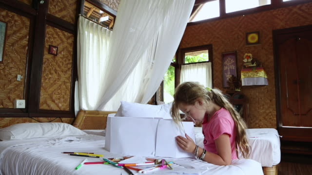 MS Shot of young girl working on art project in her bedroom / Ubud, Bali, Indonesia