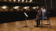 WS Shot of young male cellist practicing solo piece on stage in empty concert hall AUDIO / Ann Arbor, Michigan, United States
