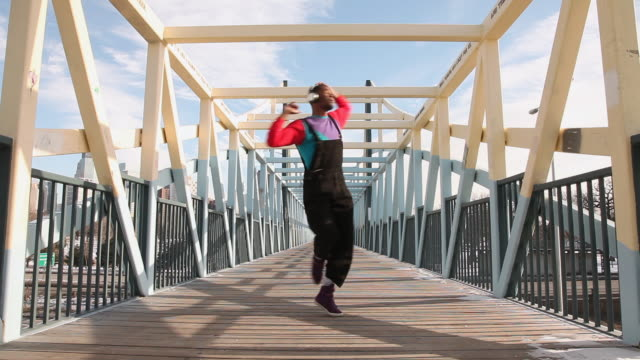 MS Shot of young man dancing on bridge in urban area / Minneapolis, Minnesota, United States