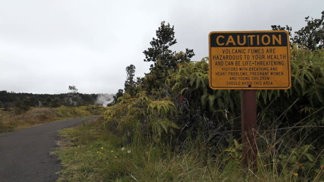 MS Shot of young man in hiking clothes walking away from path beside caution sign regarding dangerous volcanic fumes at steam vents in Volcanoes National Park / Volcano, Hawall, Big Island, United States
