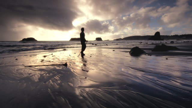 MS TS Shot of Young man walking on beach at sunset / Port Orford, Oregon, United States