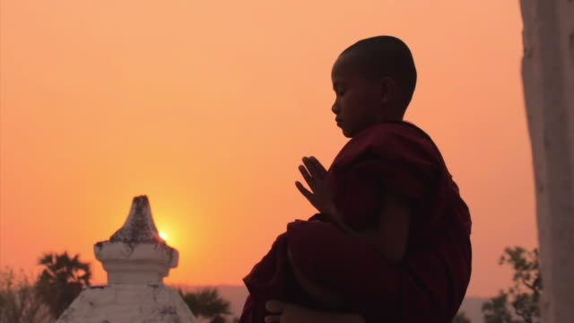 MS Shot of young monk praying (seen from the side), sunset on the background  / Mandalay, Mandalay Division, Myanmar