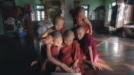 MS Shot of Young monks sitting around laptop, smiling and laughing / Yangon, Yangon Division, Myanmar