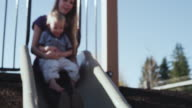 MS R/F SLO MO Shot of young mother parent going down slide on playground with her toddler baby / Beaverton, Oregon, United States