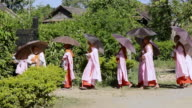 MS Shot of Young Nuns collecting alms and walking toward / Nyaungshwe, Shan State, Myanmar