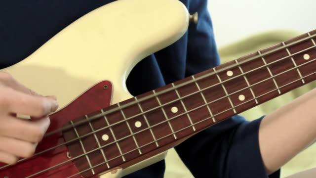 CU PAN Shot of young woman playing bass guitar in her room / Nakano, Tokyo, Japan