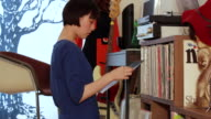 MS Shot of young woman select a Vinyl Record and putting on turntable in her room / Nakano, Tokyo, Japan