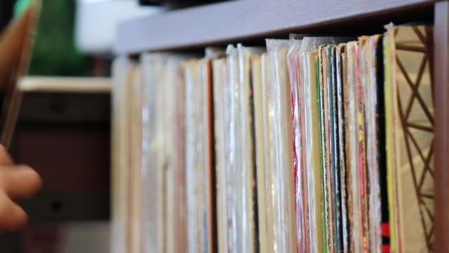 CU Shot of young woman selecting a Vinyl Record and putting on turntable in her room / Nakano, Tokyo, Japan