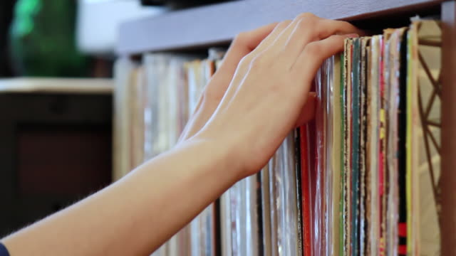CU Shot of young woman selecting a Vinyl Record in her room / Nakano, Tokyo, Japan