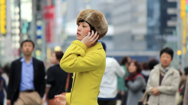 MS Shot of young woman talking on smartphone in crowd / Ginza, Tokyo, Japan
