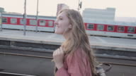 'CU POV Shot of Young woman walking and listening to music on platform central station / Berlin, Germany'