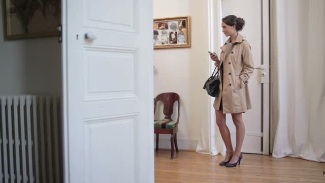MS Shot of Young woman with bag and coat standing in hallway texting / Toulouse, Haute Garonne, France