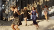 'WS PAN SLO MO Shot of Young women running inside abandoned building / Berlin, Germany'