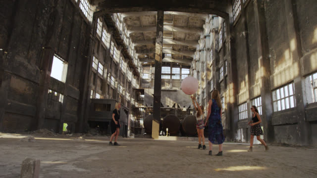 'WS HA SLO MO Shot over 1Four women playing with big pink balloon in abandoned factory / Berlin, Germany'