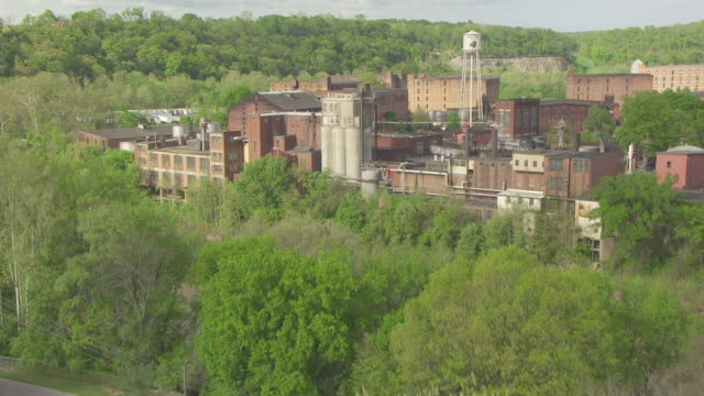 MS AERIAL TU Shot over grass field and up over Buffalo Trace Distillery / Frankfort, Kentucky, United States