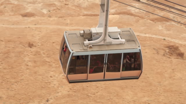 MS TS HA Shot over passengers riding cable car up Masada in Negev desert / Israel
