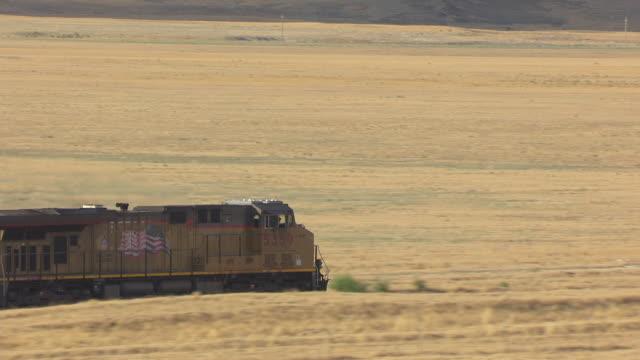 MS AERIAL TS Shot over tracking train traveling southwest of Great Salt lake en route from Salt lake City to Bonneville Salt Flats / Utah, United States