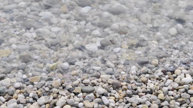 MS Shot over Water washes over pebbles beach / Bardolino, Verona, Italy