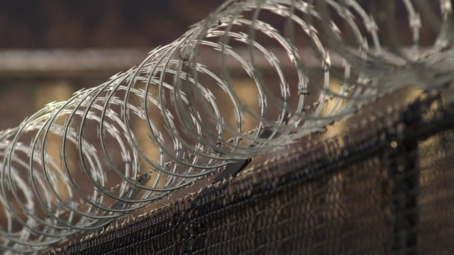 Shot starts on a black fence and tilts up revealing the razor wire lining the top