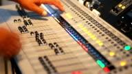 2 Shots Hand adjusting audio mixer control panel.