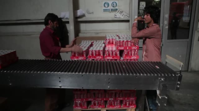 Shots of CocaCola employees stacking pallets of CocaCola cans as they come off the assembly line at Habib Gulzar NonAlcoholic Beverage Limited the...