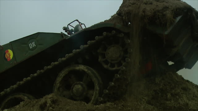 Shots of digger tank of the GDR army NVA driving through muddy ground and working / 1202008