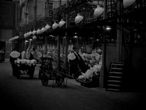Shots of general activity within Smithfield meat market including porters carrying animal carcasses