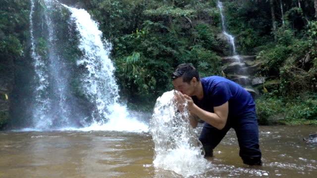 SLO-MO-2 Aufnahmen von Menschen, die mit Wasser vom Wasserfall, um sein Gesicht zu waschen