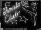 Shots of neon illuminated signs for revue and striptease clubs in London 1959