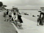 Shots of people relaxing and enjoying themselves on the beach and promenade at Cowes 1954